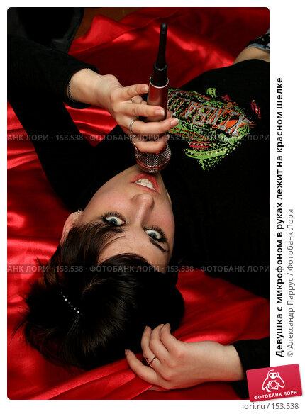Девушка с микрофоном в руках лежит на красном шелке, фото № 153538, снято 4 мая 2007 г. (c) Александр Паррус / Фотобанк Лори