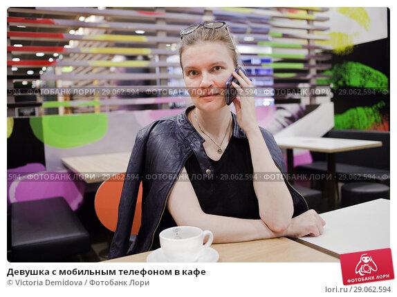 Купить «Девушка с мобильным телефоном в кафе», фото № 29062594, снято 26 августа 2018 г. (c) Victoria Demidova / Фотобанк Лори