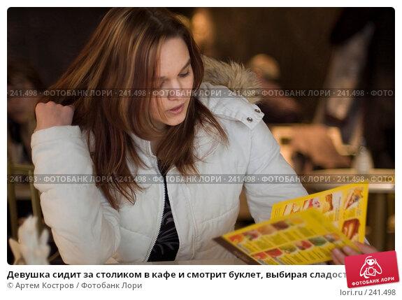 Девушка сидит за столиком в кафе и смотрит буклет, выбирая сладости, фото № 241498, снято 28 марта 2008 г. (c) Артем Костров / Фотобанк Лори