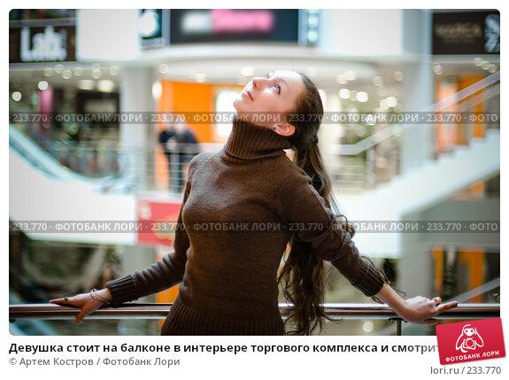 Девушка стоит на балконе в интерьере торгового комплекса и смотрит вверх, фото № 233770, снято 5 марта 2008 г. (c) Артем Костров / Фотобанк Лори