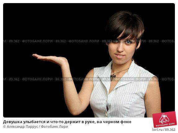 Девушка улыбается и что-то держит в руке, на черном фоне, фото № 89362, снято 31 мая 2007 г. (c) Александр Паррус / Фотобанк Лори