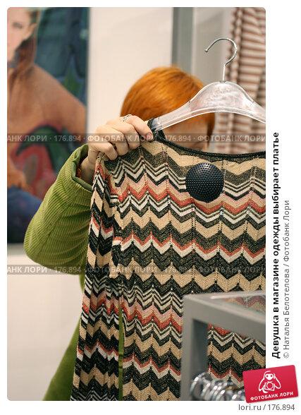 Девушка в магазине одежды выбирает платье, фото № 176894, снято 13 октября 2007 г. (c) Наталья Белотелова / Фотобанк Лори