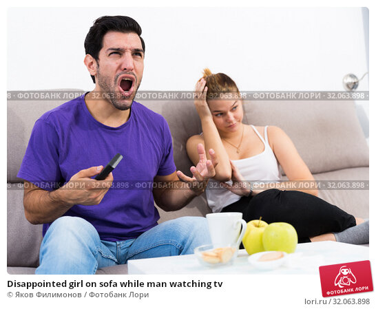 Disappointed girl on sofa while man watching tv. Стоковое фото, фотограф Яков Филимонов / Фотобанк Лори