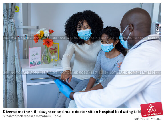 Diverse mother, ill daughter and male doctor sit on hospital bed using tablet, wearing face masks. Стоковое фото, агентство Wavebreak Media / Фотобанк Лори