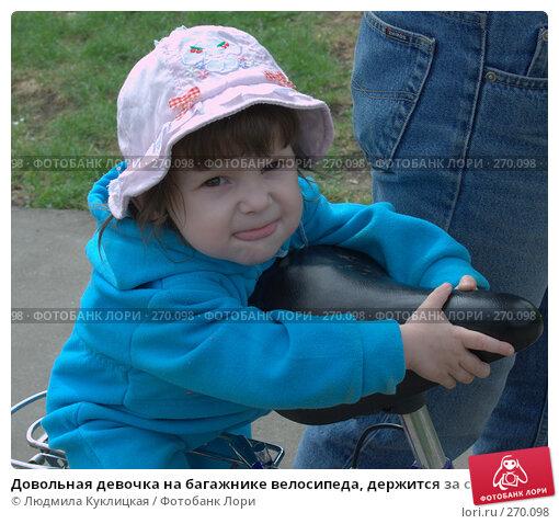 Довольная девочка на багажнике велосипеда, держится за сиденье, фото № 270098, снято 30 апреля 2008 г. (c) Людмила Куклицкая / Фотобанк Лори