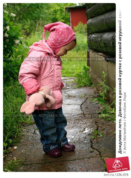 Дождливое лето. Девочка в розовой куртке с розовой игрушкой  смотрит в лужу, фото № 236474, снято 27 июня 2007 г. (c) Алла Матвейчик / Фотобанк Лори
