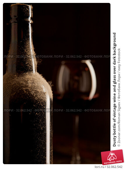 Dusty bottle of vintage wine and glass over dark background. Стоковое фото, фотограф Zoonar.com/Roman Sigaev / easy Fotostock / Фотобанк Лори