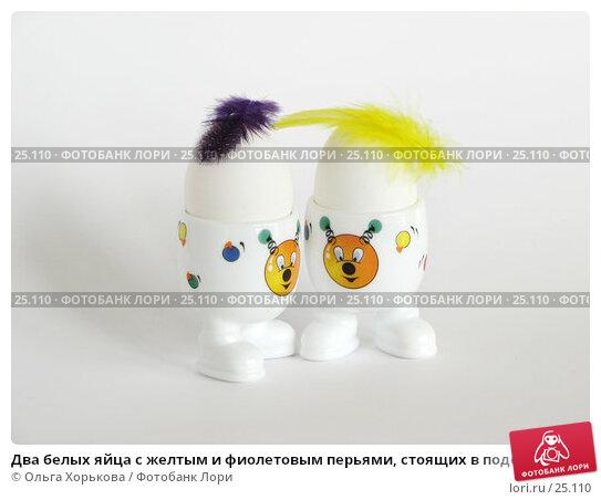 Два белых яйца с желтым и фиолетовым перьями, стоящих в подставках с веселыми рожицами, фото № 25110, снято 20 марта 2007 г. (c) Ольга Хорькова / Фотобанк Лори