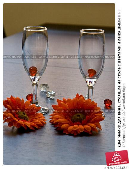 Купить «Две рюмки для вина, стоящие на столе с цветами и лежащими в них кусочками красного стекла», фото № 223634, снято 22 марта 2018 г. (c) Баевский Дмитрий / Фотобанк Лори