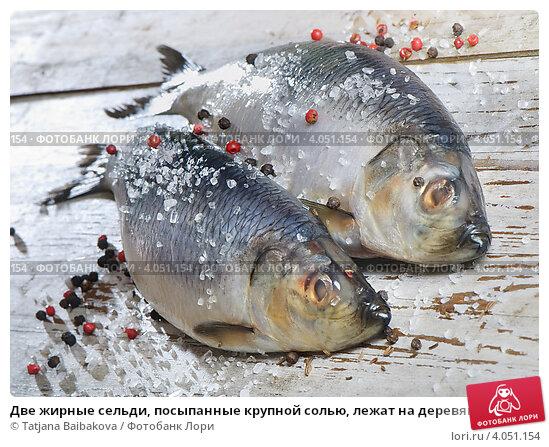 Купить «Две жирные сельди, посыпанные крупной солью, лежат на деревянном столе», фото № 4051154, снято 29 января 2012 г. (c) Tatjana Baibakova / Фотобанк Лори