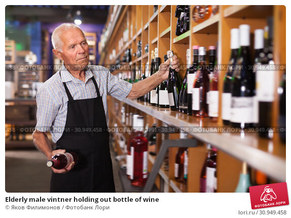 Купить «Elderly male vintner holding out bottle of wine», фото № 30949458, снято 8 мая 2019 г. (c) Яков Филимонов / Фотобанк Лори