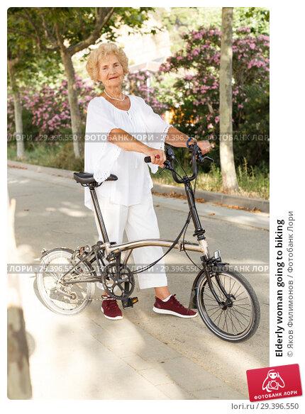 Купить «Elderly woman going to biking», фото № 29396550, снято 6 июля 2018 г. (c) Яков Филимонов / Фотобанк Лори