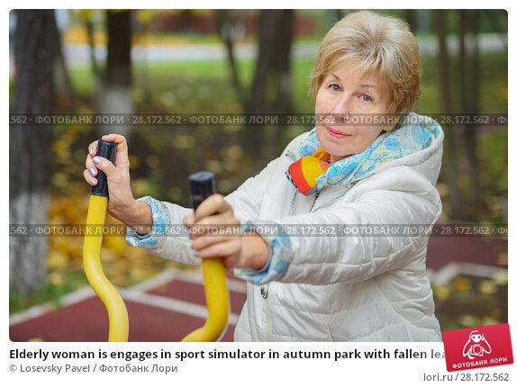 Купить «Elderly woman is engages in sport simulator in autumn park with fallen leaves», фото № 28172562, снято 6 октября 2016 г. (c) Losevsky Pavel / Фотобанк Лори