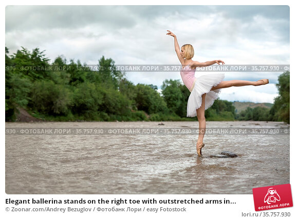 Elegant ballerina stands on the right toe with outstretched arms in... Стоковое фото, фотограф Zoonar.com/Andrey Bezuglov / easy Fotostock / Фотобанк Лори