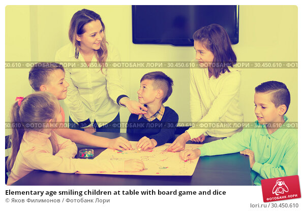 Elementary age smiling children at table with board game and dice. Стоковое фото, фотограф Яков Филимонов / Фотобанк Лори