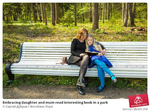 Купить «Embracing daughter and mum read interesting book in a park», фото № 28631310, снято 21 мая 2017 г. (c) Сергей Дубров / Фотобанк Лори