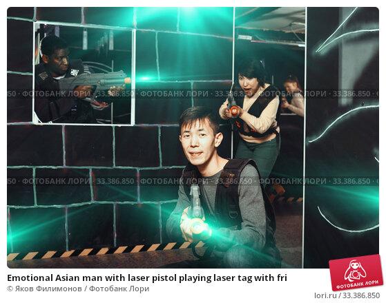 Купить «Emotional Asian man with laser pistol playing laser tag with fri», фото № 33386850, снято 23 января 2019 г. (c) Яков Филимонов / Фотобанк Лори