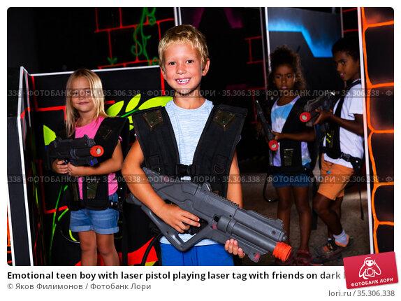 Emotional teen boy with laser pistol playing laser tag with friends on dark labyrinth. Стоковое фото, фотограф Яков Филимонов / Фотобанк Лори