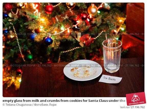 Купить «empty glass from milk and crumbs from cookies for Santa Claus under the Christmas tree with lights, close-up», фото № 27196762, снято 12 мая 2017 г. (c) Tetiana Chugunova / Фотобанк Лори