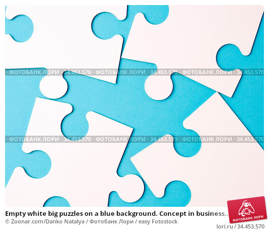 Empty white big puzzles on a blue background. Concept in business... Стоковое фото, фотограф Zoonar.com/Danko Natalya / easy Fotostock / Фотобанк Лори