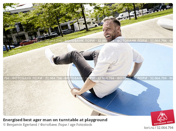 Energised best ager man on turntable at playground. Стоковое фото, фотограф Benjamin Egerland / age Fotostock / Фотобанк Лори