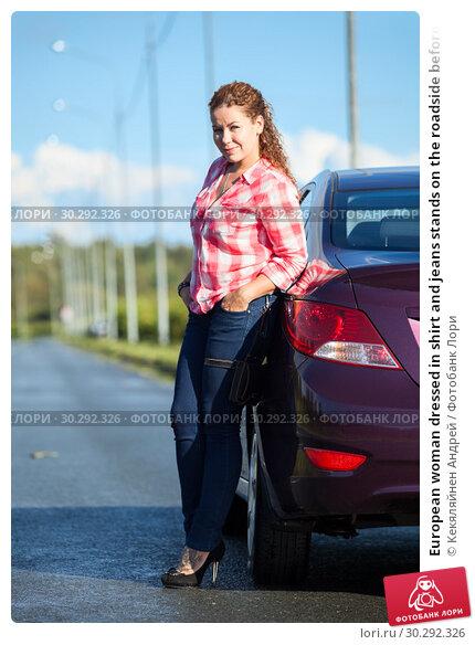 Купить «European woman dressed in shirt and jeans stands on the roadside before parked car, full-length portrait», фото № 30292326, снято 12 августа 2016 г. (c) Кекяляйнен Андрей / Фотобанк Лори
