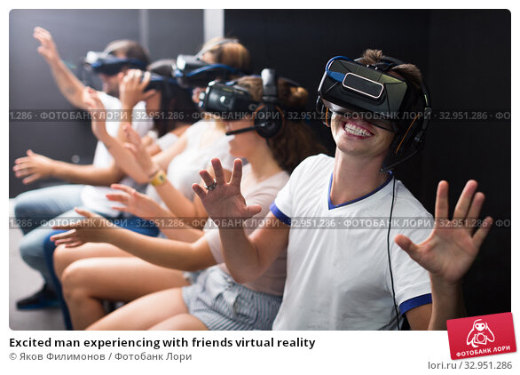 Excited man experiencing with friends virtual reality. Стоковое фото, фотограф Яков Филимонов / Фотобанк Лори