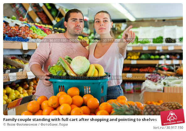 Купить «Family couple standing with full cart after shopping and pointing to shelves», фото № 30917150, снято 27 апреля 2019 г. (c) Яков Филимонов / Фотобанк Лори