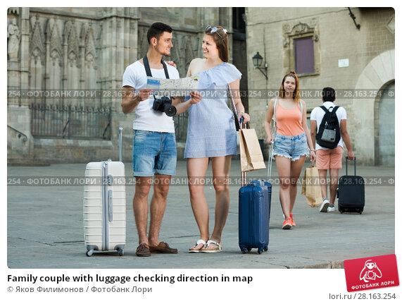 Купить «Family couple with luggage checking direction in map», фото № 28163254, снято 22 июня 2017 г. (c) Яков Филимонов / Фотобанк Лори