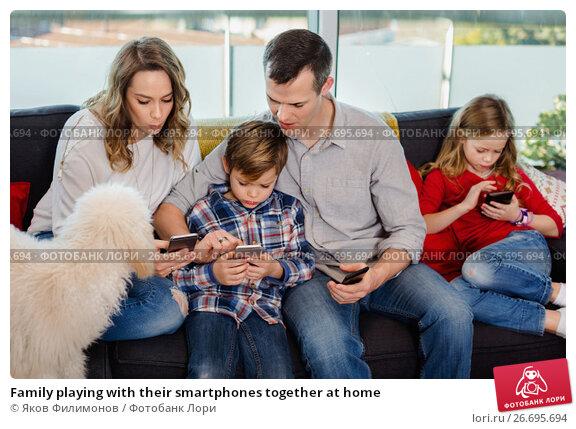 Купить «Family playing with their smartphones together at home», фото № 26695694, снято 23 декабря 2016 г. (c) Яков Филимонов / Фотобанк Лори