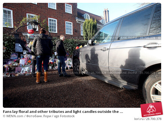 Купить «Fans lay floral and other tributes and light candles outside the home of singer George Michael in memory of the popular performer. His Range Rover has...», фото № 28700378, снято 28 декабря 2016 г. (c) age Fotostock / Фотобанк Лори