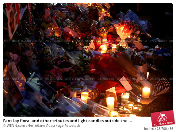 Купить «Fans lay floral and other tributes and light candles outside the home of singer George Michael in memory of the popular performer. His Range Rover has...», фото № 28700486, снято 28 декабря 2016 г. (c) age Fotostock / Фотобанк Лори