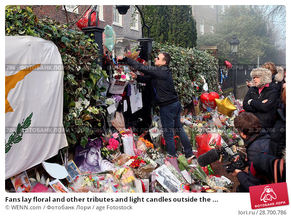 Купить «Fans lay floral and other tributes and light candles outside the home of singer George Michael in memory of the popular performer. His Range Rover has...», фото № 28700786, снято 28 декабря 2016 г. (c) age Fotostock / Фотобанк Лори