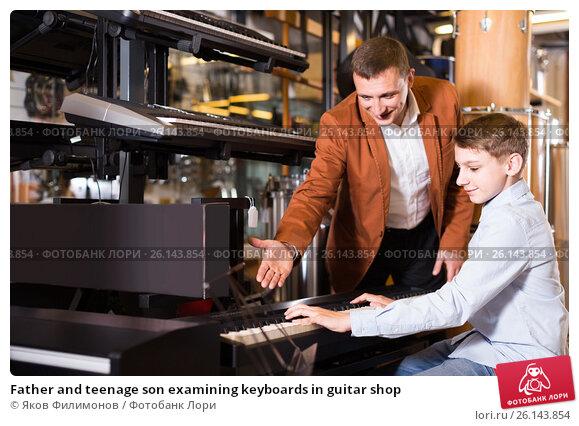 Купить «Father and teenage son examining keyboards in guitar shop», фото № 26143854, снято 29 марта 2017 г. (c) Яков Филимонов / Фотобанк Лори