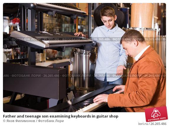 Купить «Father and teenage son examining keyboards in guitar shop», фото № 26265486, снято 29 марта 2017 г. (c) Яков Филимонов / Фотобанк Лори