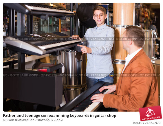 Купить «Father and teenage son examining keyboards in guitar shop», фото № 27152970, снято 29 марта 2017 г. (c) Яков Филимонов / Фотобанк Лори