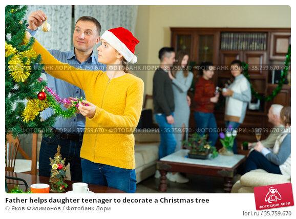 Father helps daughter teenager to decorate a Christmas tree. Стоковое фото, фотограф Яков Филимонов / Фотобанк Лори