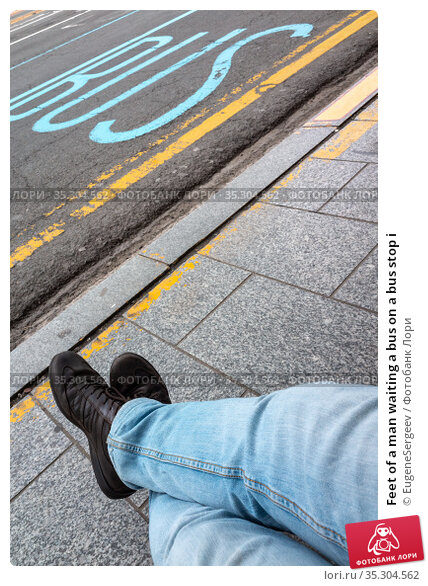 Feet of a man waiting a bus on a bus stop i. Стоковое фото, фотограф EugeneSergeev / Фотобанк Лори