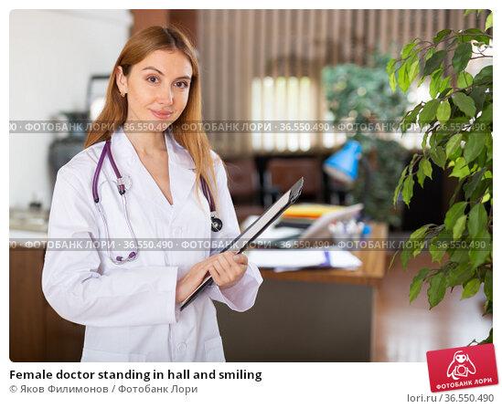 Female doctor standing in hall and smiling. Стоковое фото, фотограф Яков Филимонов / Фотобанк Лори