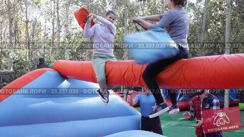 Female friends having funny wrestling by pillows on inflatable beam in outdoor amusement park. Стоковое видео, видеограф Яков Филимонов / Фотобанк Лори