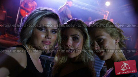 Купить «Female friends posing together at a concert 4k», видеоролик № 29704242, снято 7 марта 2017 г. (c) Wavebreak Media / Фотобанк Лори