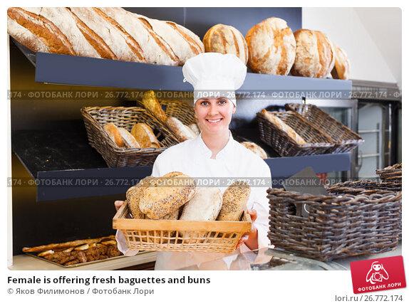 Купить «Female is offering fresh baguettes and buns», фото № 26772174, снято 22 апреля 2017 г. (c) Яков Филимонов / Фотобанк Лори