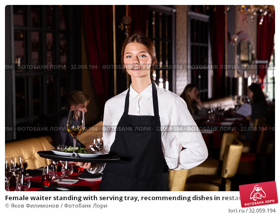 Female waiter standing with serving tray, recommending dishes in restaurant. Стоковое фото, фотограф Яков Филимонов / Фотобанк Лори