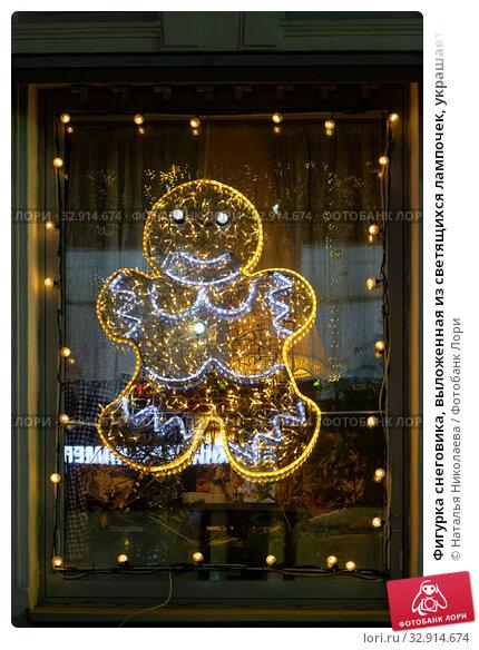 Фигурка снеговика, выложенная из светящихся лампочек, украшает окно кафе (2020 год). Редакционное фото, фотограф Наталья Николаева / Фотобанк Лори
