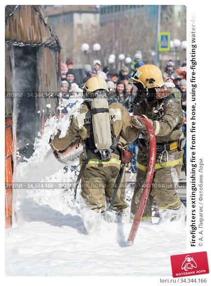 Firefighters extinguishing fire from fire hose, using fire-fighting water-foam barrel with air-mechanical foam (2019 год). Редакционное фото, фотограф А. А. Пирагис / Фотобанк Лори