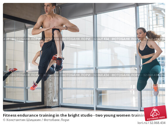 Fitness endurance training in the bright studio - two young women training with their coach - jumping exercises. Стоковое фото, фотограф Константин Шишкин / Фотобанк Лори