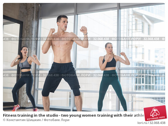 Fitness training in the studio - two young women training with their athletic coach - boxing. Стоковое фото, фотограф Константин Шишкин / Фотобанк Лори