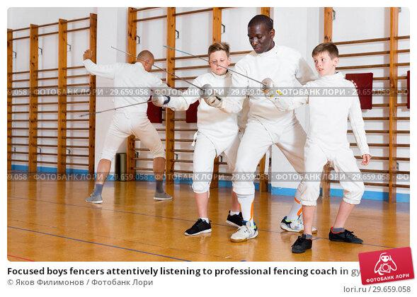 Купить «Focused boys fencers attentively listening to professional fencing coach in gym», фото № 29659058, снято 30 мая 2018 г. (c) Яков Филимонов / Фотобанк Лори