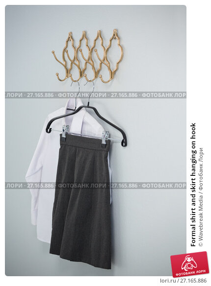Купить «Formal shirt and skirt hanging on hook», фото № 27165886, снято 25 августа 2017 г. (c) Wavebreak Media / Фотобанк Лори