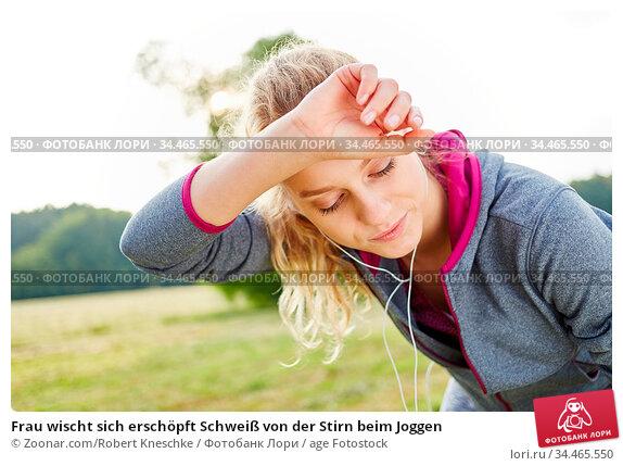 Frau wischt sich erschöpft Schweiß von der Stirn beim Joggen. Стоковое фото, фотограф Zoonar.com/Robert Kneschke / age Fotostock / Фотобанк Лори